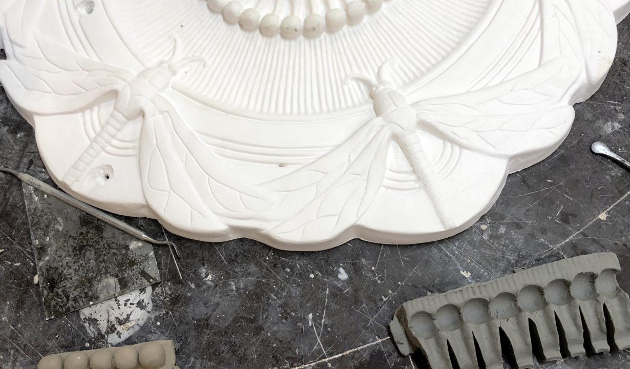 Modellert støvknapp i leire og trykkform i plastelina.